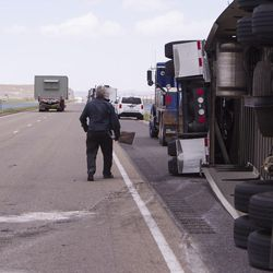 Bob Williams cleans the road after semitrailer was toppled by the wind on I-80 near Dugway on Monday, June 12, 2017.