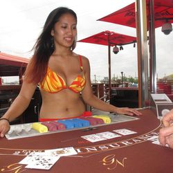 Jessica Sangreo, a newly hired dealer at the Golden Nugget in Atlantic City, N.J., practices dealing blackjack hands on a specially equipped outdoor table with wires to prevent cards from blowing away Wednesday, Sept. 5, 2012. The Golden Nugget is the first casino in Atlantic City to get permission to offer gambling outdoors.