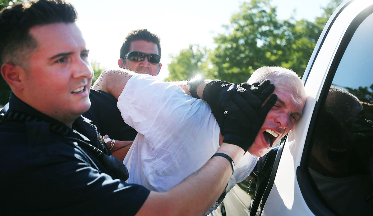 Aaron James is taken into custody after police and marchers collided in the streets of Cottonwood Heights on Sunday, Aug. 2, 2020. The group was marching on 6710 South when police blocked them at Cristobal Street and a confrontation ensued. Police said eight or nine protesters were arrested.