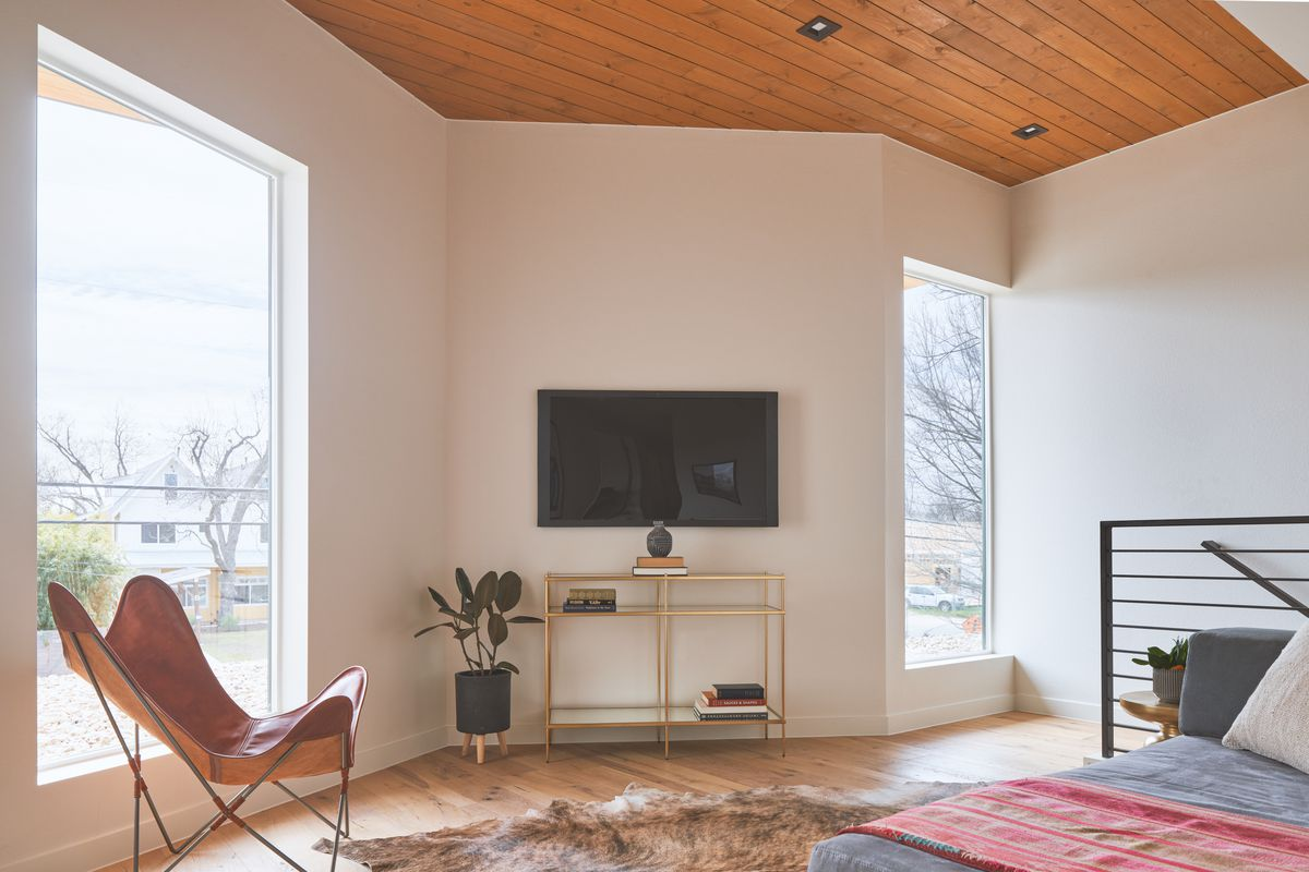 Photo of a loft bedroom with a zigzag wall featuring two large vertical picture windows. There is a bed in front of the top of the open stairwell's metal railing. A leather butterfly chair is facing the bed. The floors are wood and ahave a fur or fake fur rug on top. There's a TV on a metal stand against the wall between the windows.