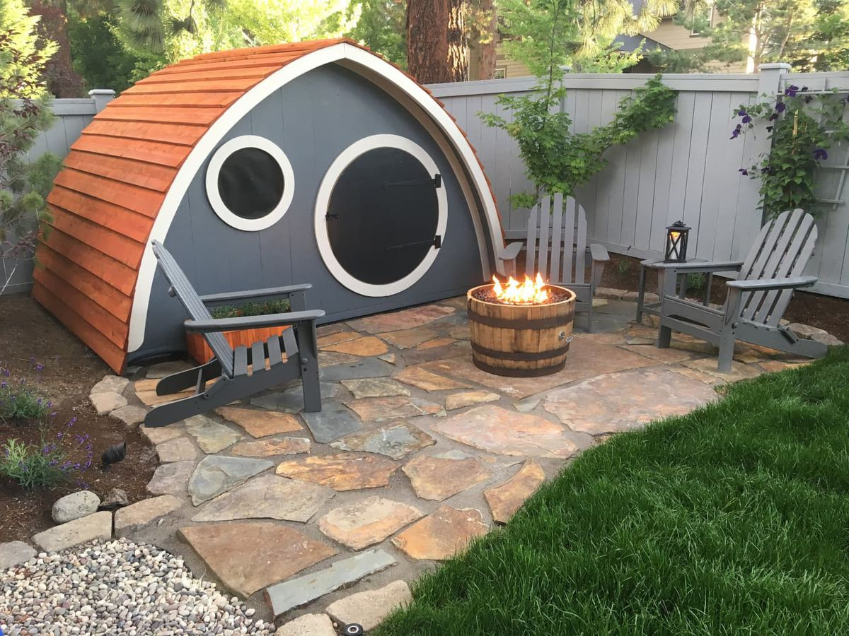 Hobbit-like house in backyard on stone paved patio.