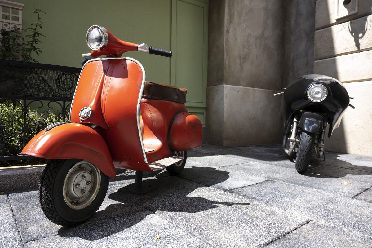 A red vespa parked next to a black motorcycle