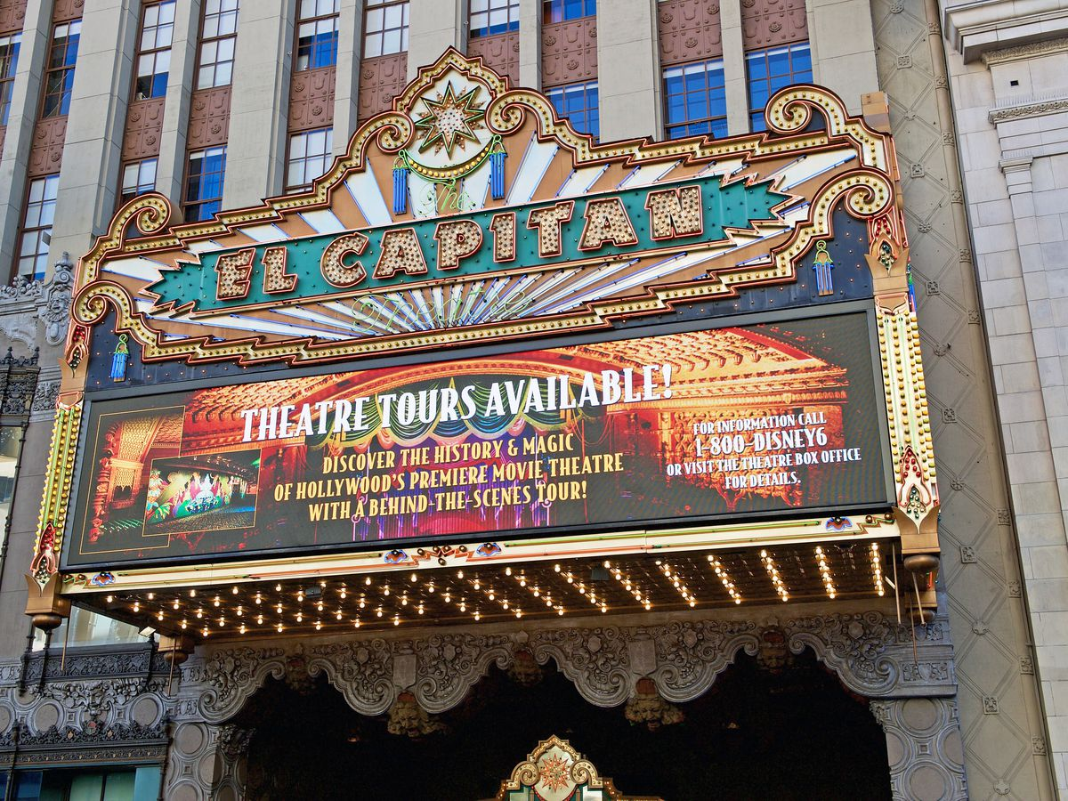 """A gilded marquee advertising theater tours. Large letters on top read """"El Capitan"""""""