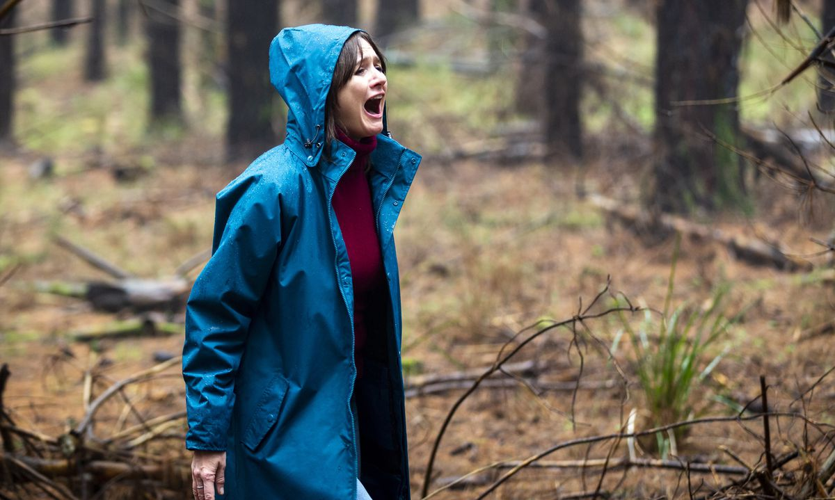 Emily Mortimer in Relic stands in the woods in a bright blue jacket, screaming.