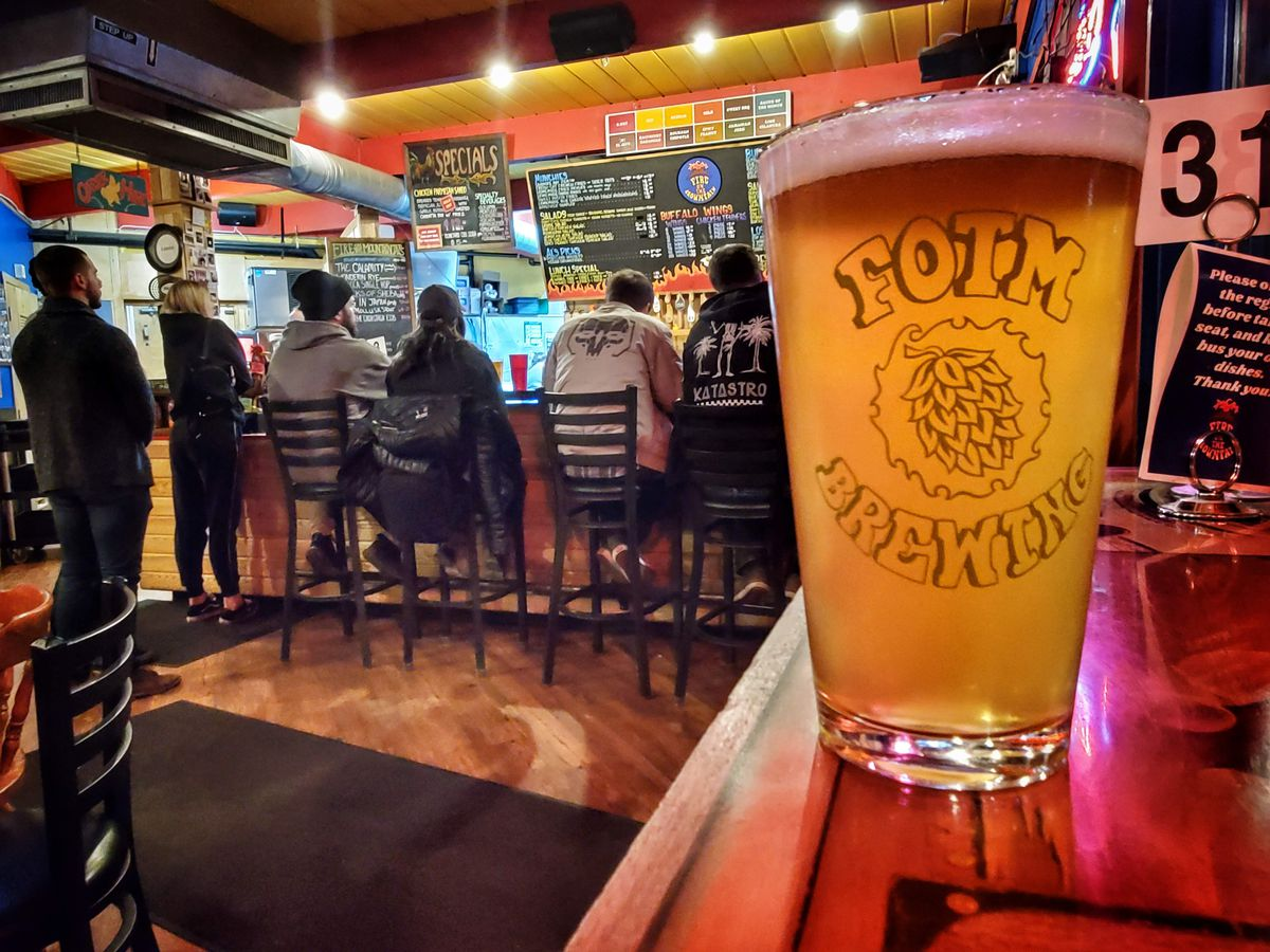 A glass of beer sits in the foreground, while in the background people are lined up and seated at the bar