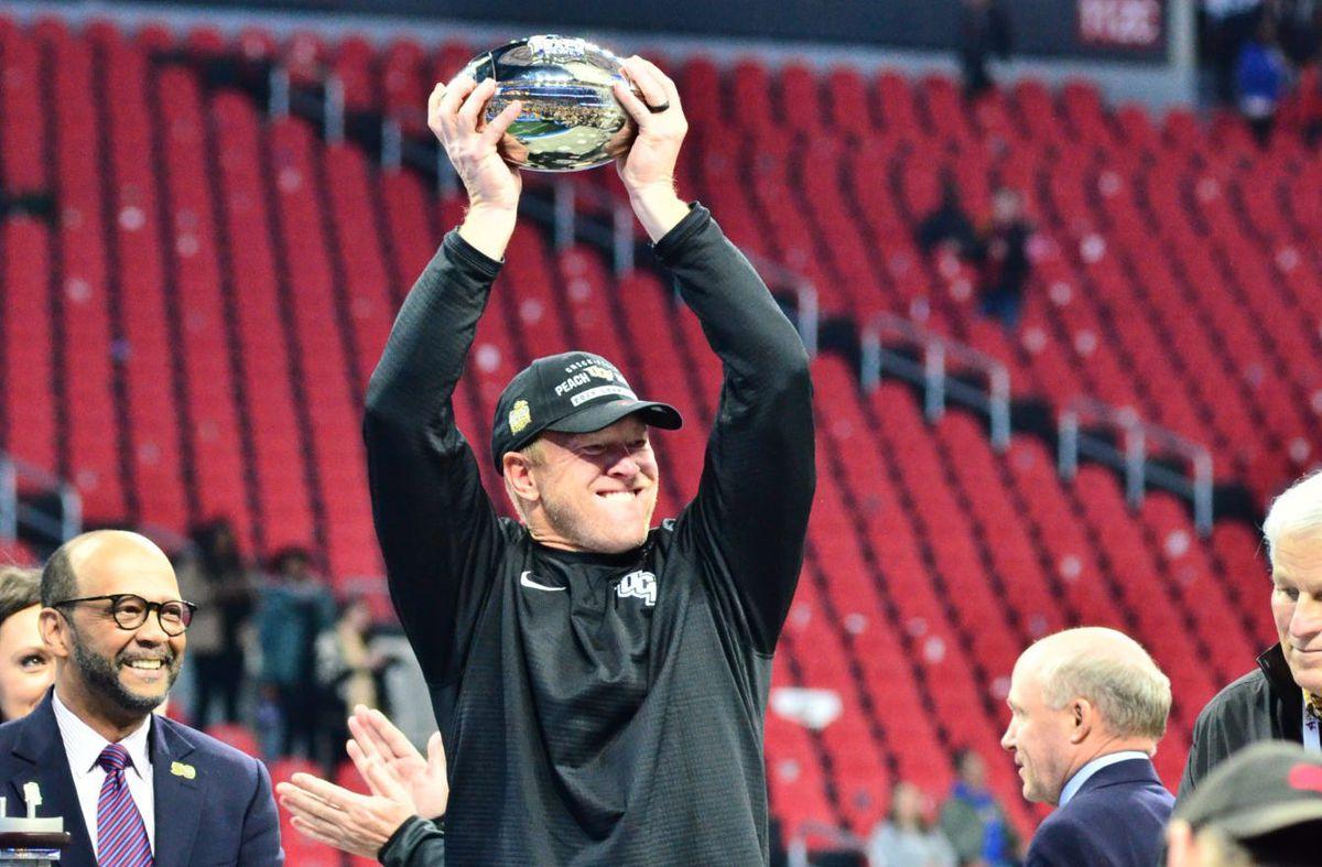 UCF head coach Scott Frost hoists the Peach Bowl championship trophy. Photo: Derek Warden)