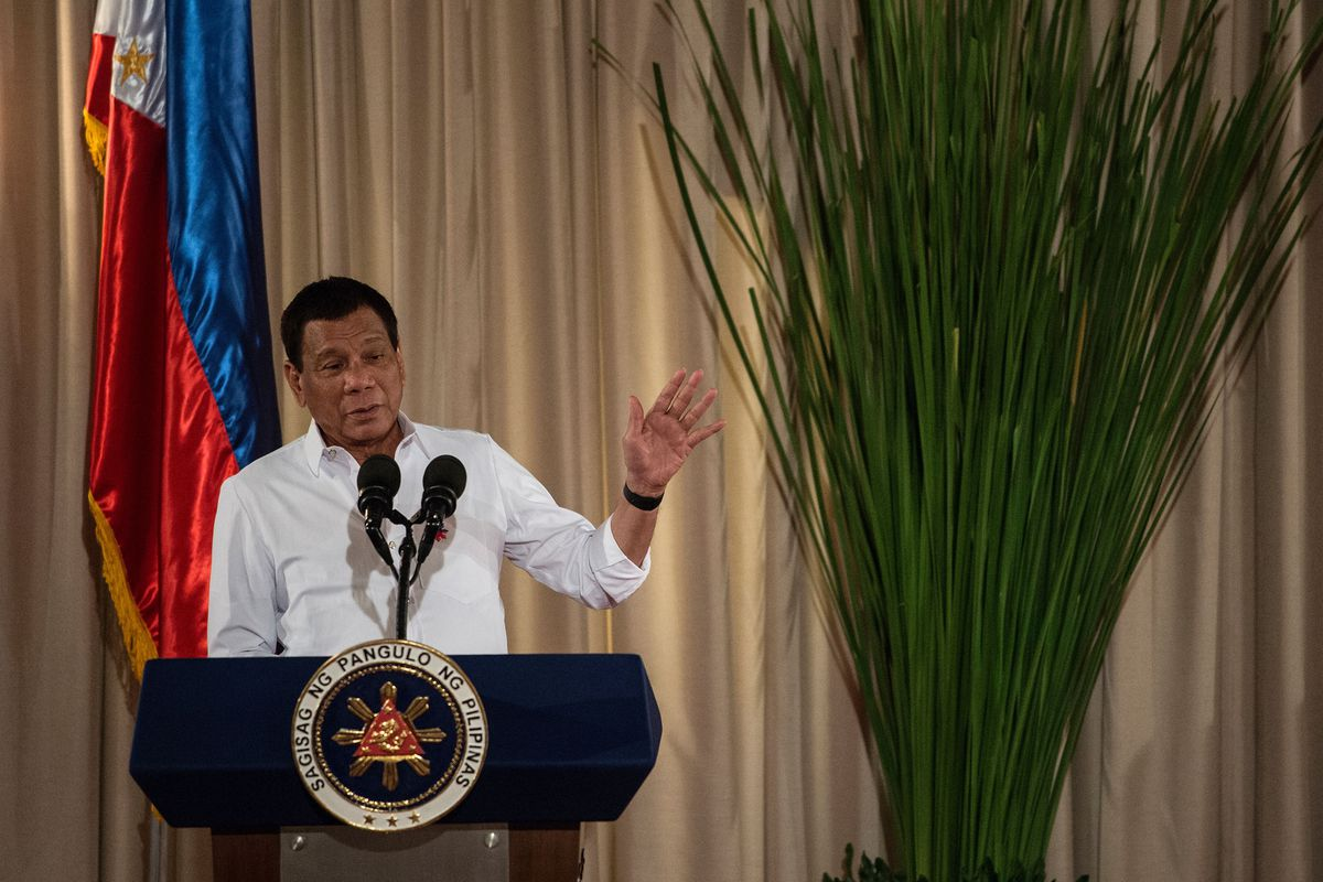 Duterte stands at a podium with the Filipino flag in the background.
