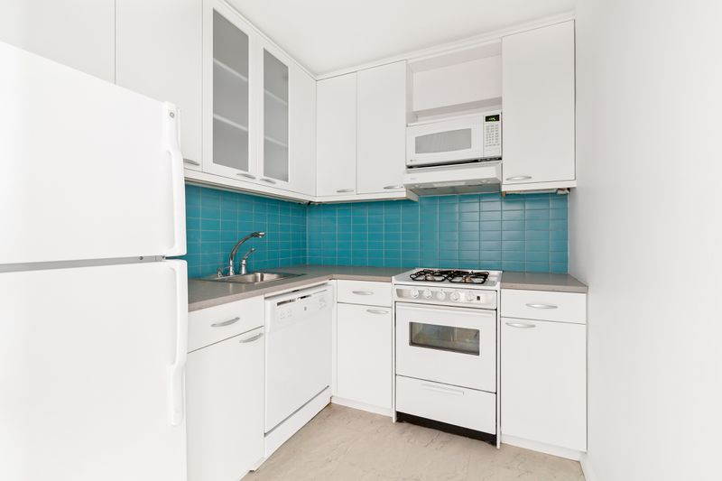 A kitchen with white cabinetry and bright blue tiles.