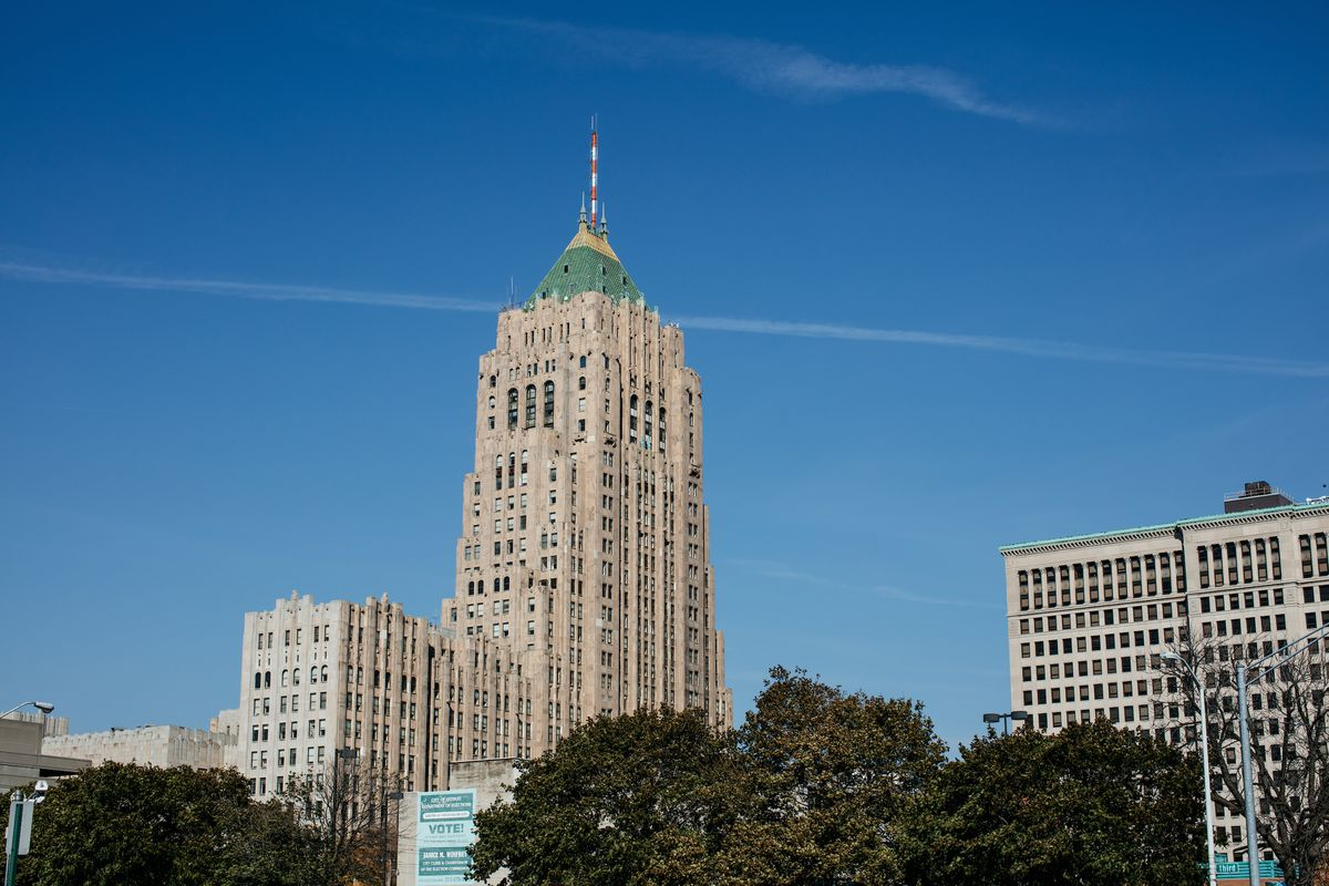 The Fisher Building—a tall, two-story stone structure—rises in the distance. There's some trees in the foreground.