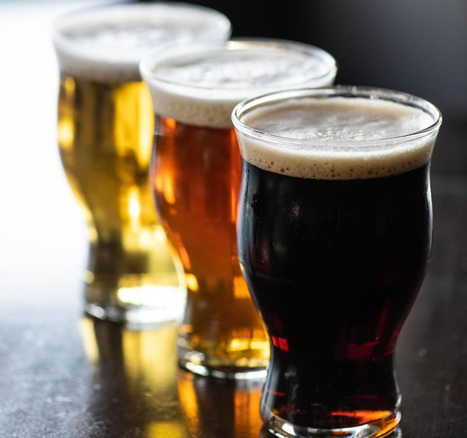 Three beers in a line on a bar
