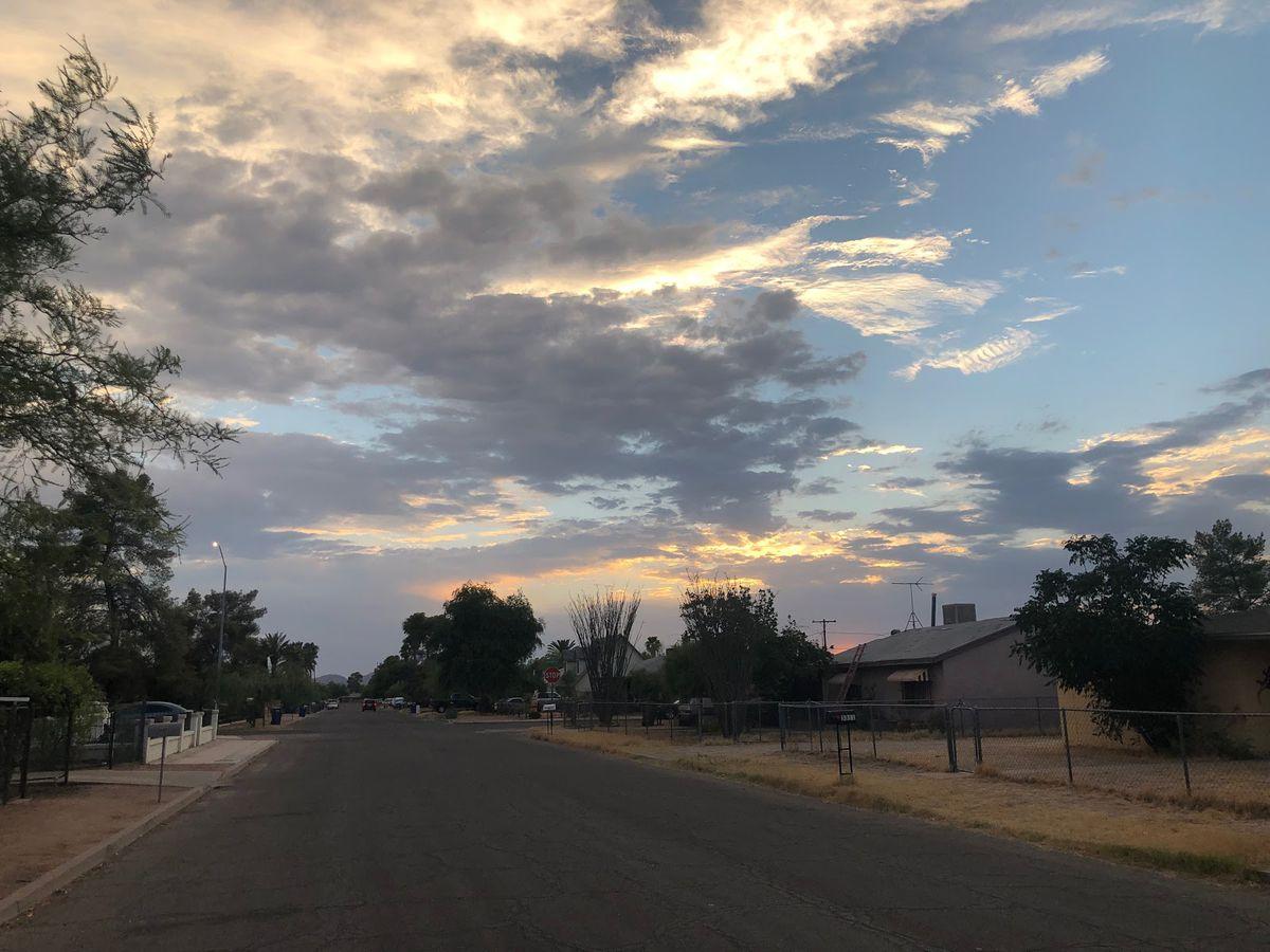 A suburban neighborhood in the desert against a cloudy twilight sky.