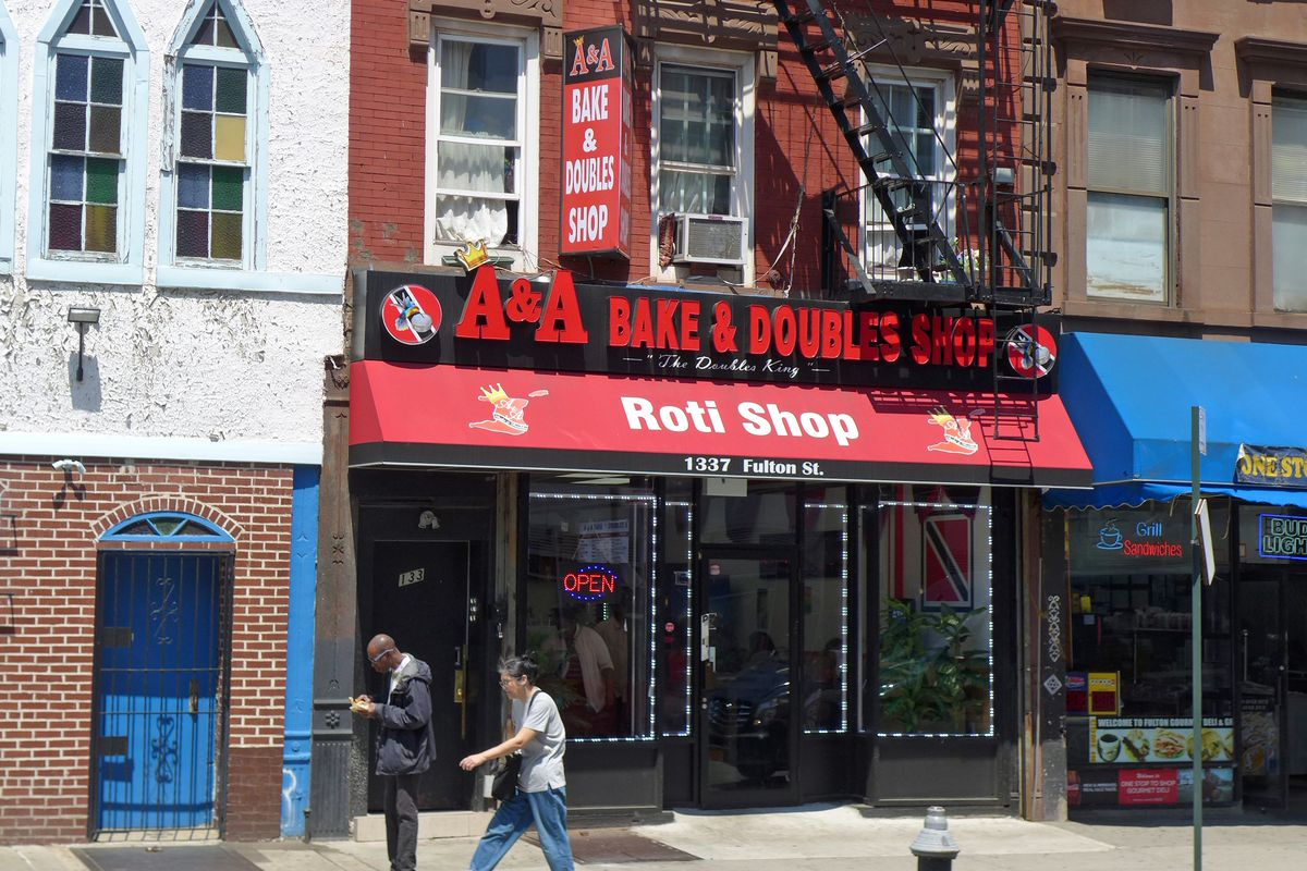 """Two people walk in front a red storefront whose neon sign reads """"A&A Bake & Doubles Roti Shop"""""""