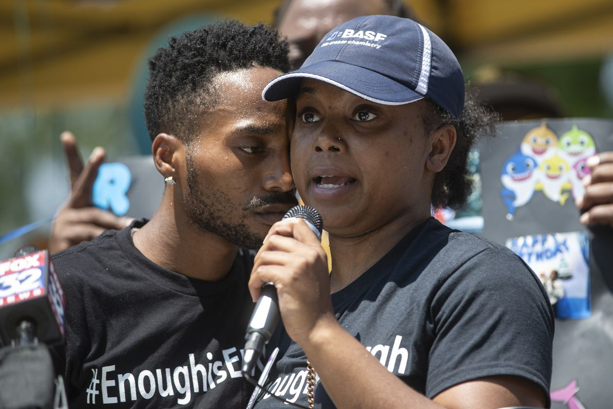 Yasmine Miller, right, speaks to the crowd with Thomas Gaston, left, at her side during a vigil for their son, Sincere A. Gaston earlier this month.
