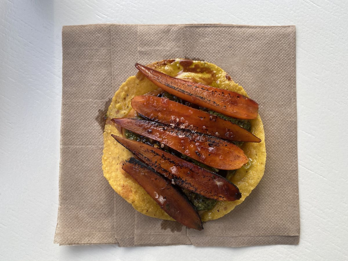 Carrots sit dolloped on a golden tostada, which sits on a brown square napkin on a white table.