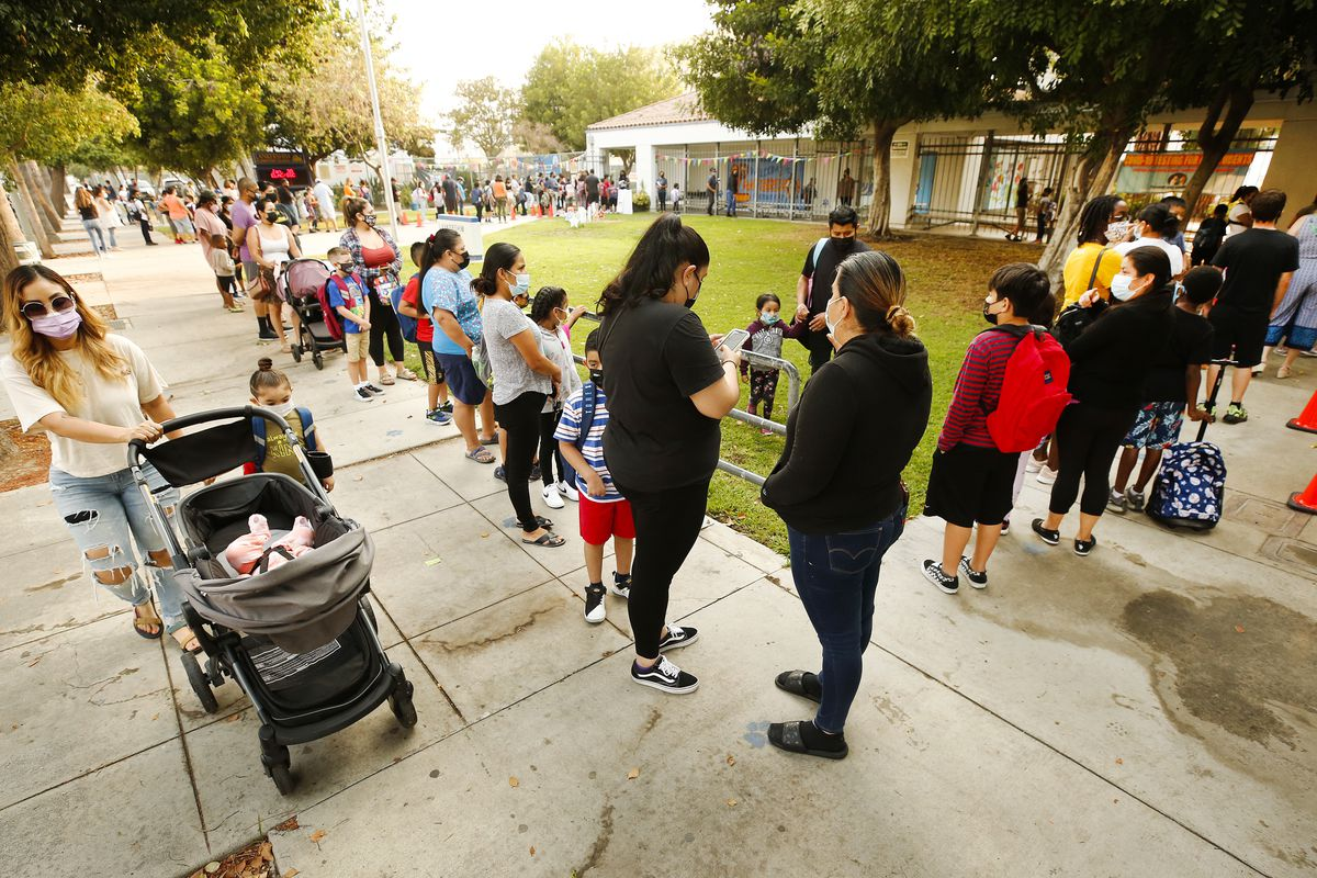 Students and parents stand in a long line outside school.
