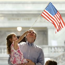 Blake Yoybal holds daughter Hannah, 3, as she waves an American flag before a naturalization ceremony at the Capitol in Salt Lake City on Thursday, Aug. 12, 2021. One hundred twenty-four citizenship candidates, including Roybal's wife, who is from Brazil, became U.S. citizens.