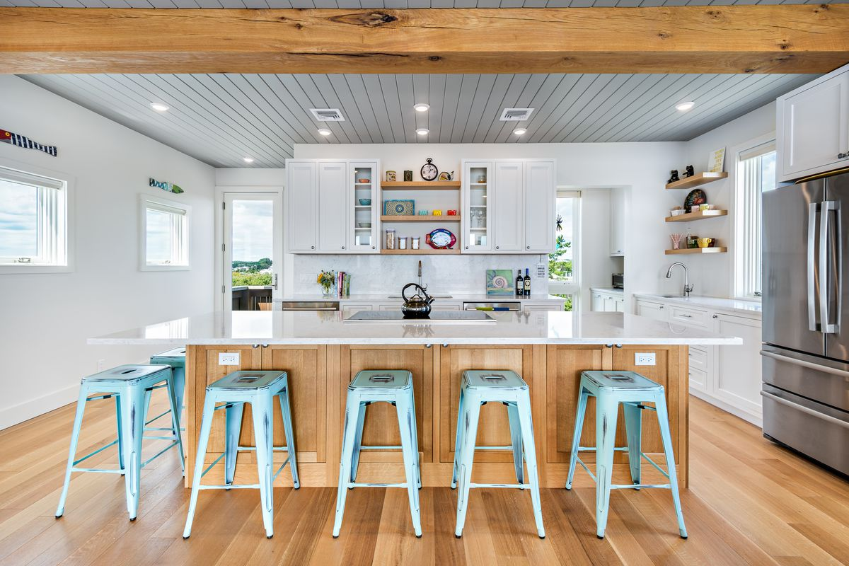 An open-concept kitchen has teal barstools at a large island, with white counters and white cabinets.