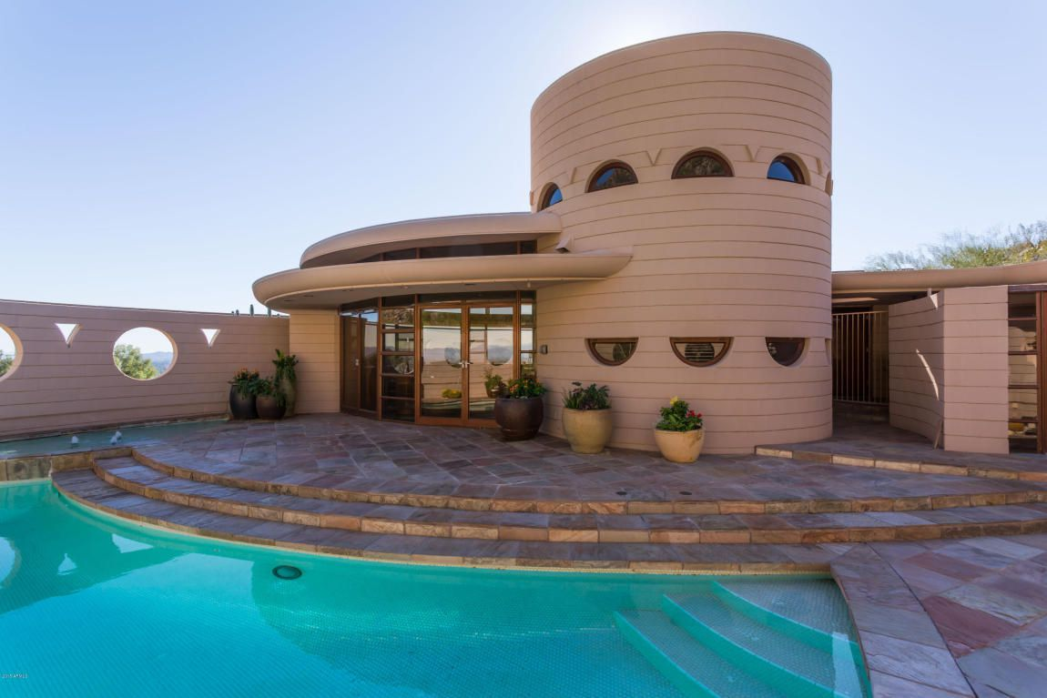 The Norman Lykes House by Frank Lloyd Wright. The exterior is circular shaped and brown. There are stairs leading up to the entrance. There is a swimming pool in the foreground.