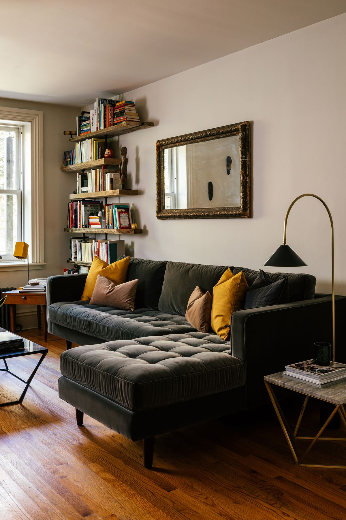 A gray, velvet-upholstered sofa has yellow pillows on it. A bookcase filled with books sits to one side, a lamp on the other.