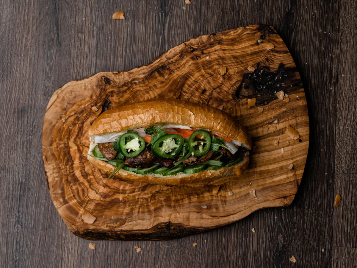 A banh mi sandwich packed with BBQ pork and pickled vegetables rests on top of a natural woodcut cutting board