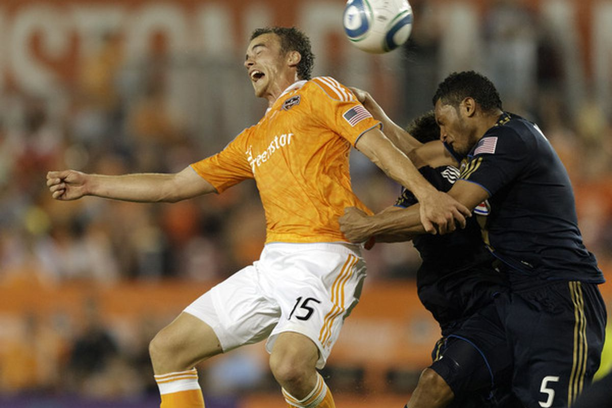 HOUSTON - MARCH 19:  Geoff Cameron #15 of the Houston Dynamo heads the ball on goal as Carlos valdes #5 of the Philadelphia Union defends in the second half at Robertson Stadium on March 19, 2011 in Houston, Texas.  (Photo by Bob Levey/Getty Images)