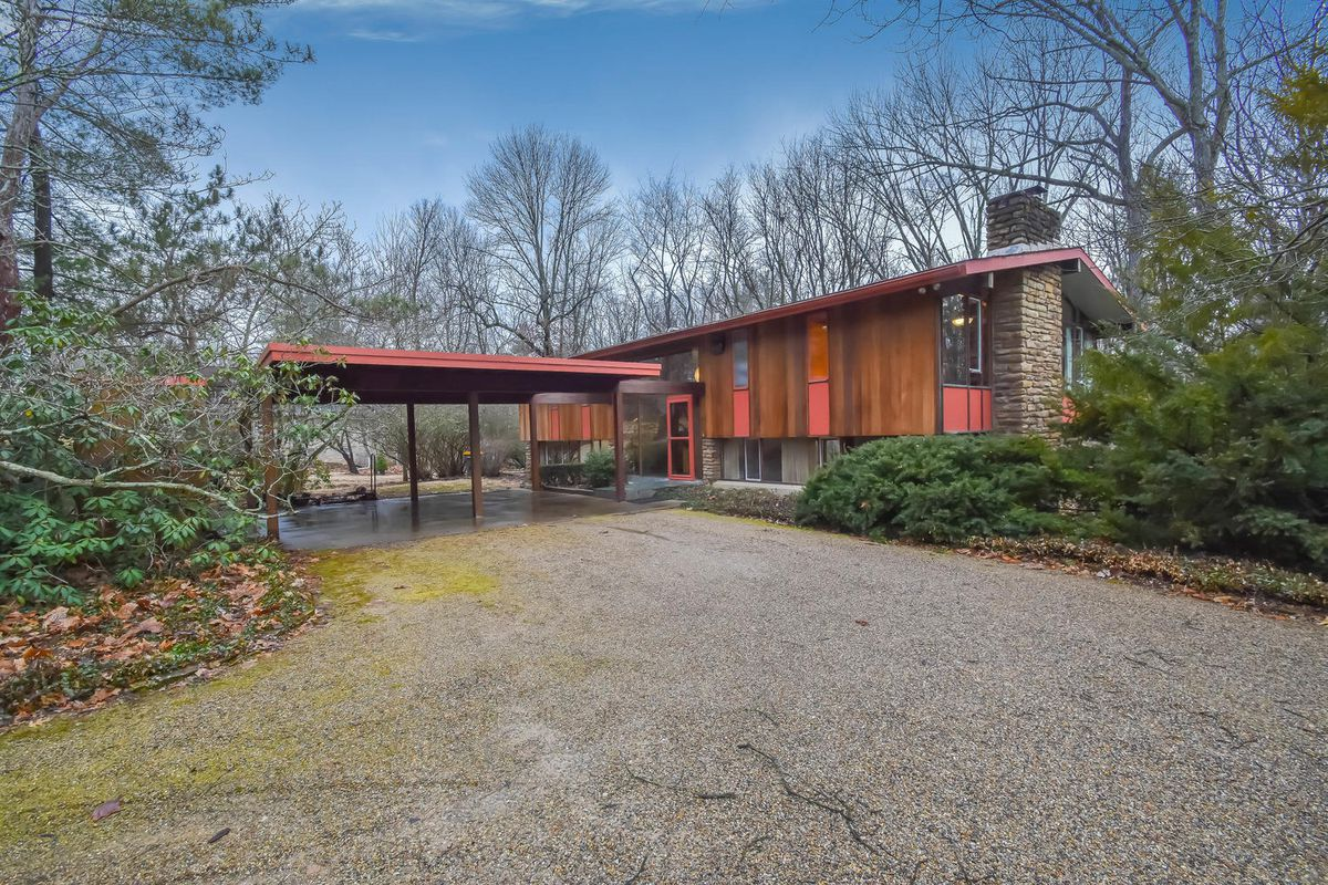 Large home with rectangular form and gable roof with wood and stone siding and carport on woodsy lot.