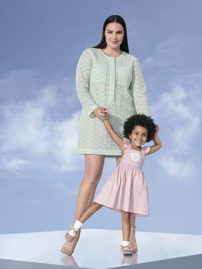 Model in mint green lace dress with small child in pink dress.