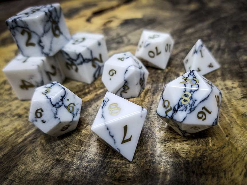 White dice with dark blue striations and brass numbers sit on a wooden table.