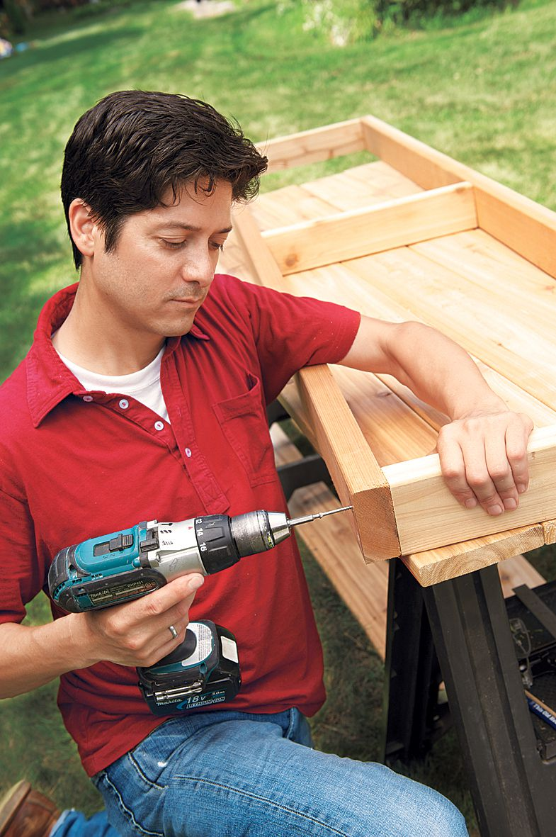 Man Assembles Seat Frame Of Planter Bench With Drill