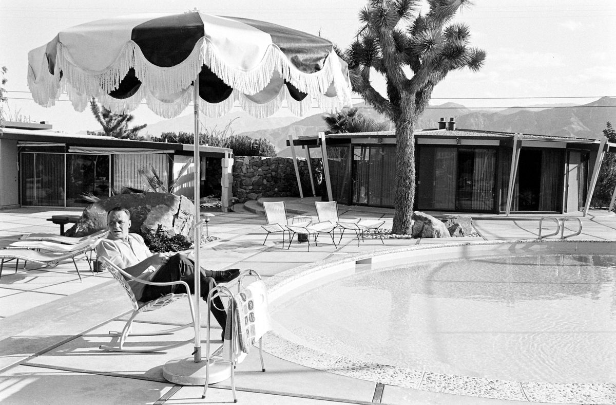 Frank Sinatra sits in a lounge chair next to a swimming pool outside of a house in Palm Springs.