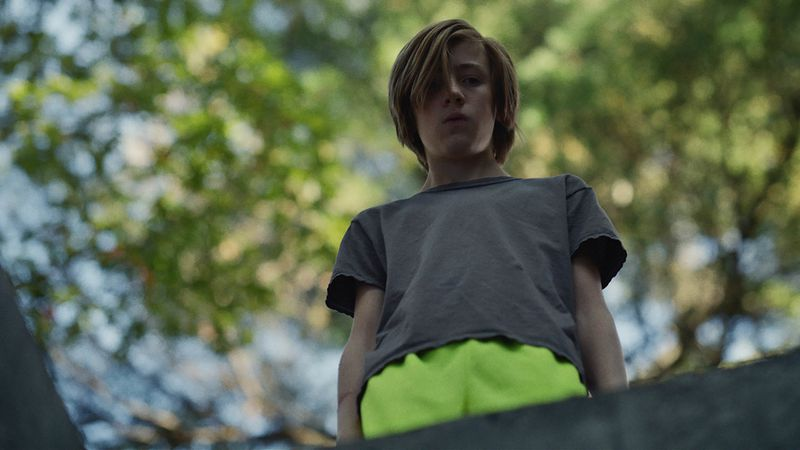A young boy stands looking down into a hole, with trees in the background.