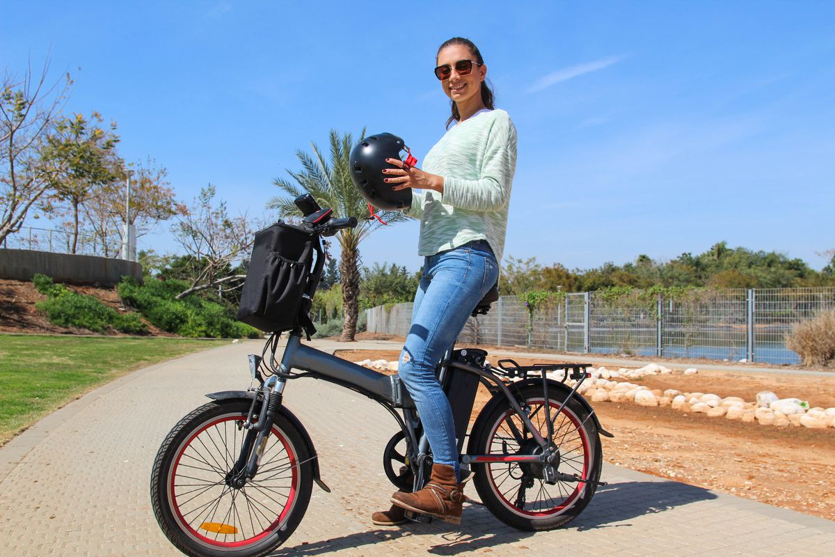 A woman poses on her electric bike on a bike path, with helmet in hand.