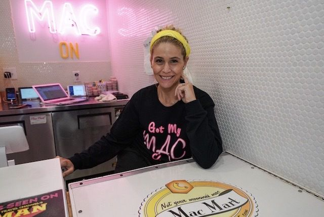 """A woman sits behind a counter in front of a neon """"Mac Mart"""" sign"""