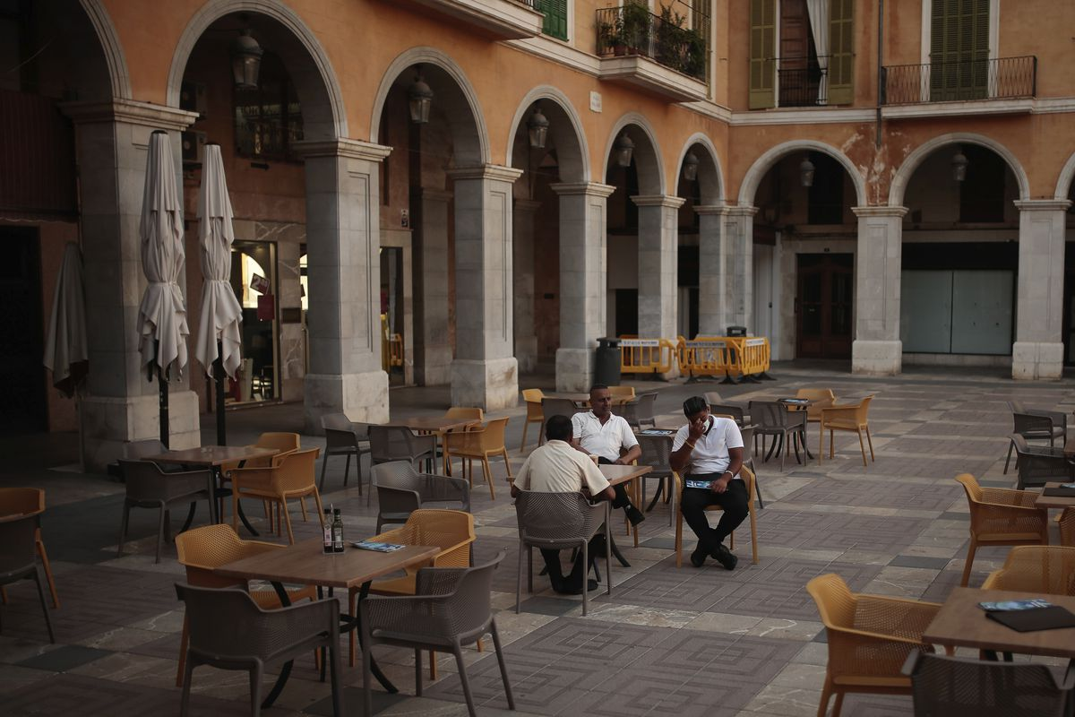 People sit in a nearly empty restaurant in the Balearic Islands capital of Palma de Mallorca, Spain, Wednesday, July 29, 2020. Concerns over a new wave of coronavirus infections brought on by returning vacationers are wreaking havoc across Spain's tourism industry, particularly in the Balearic Islands following Britain's effective ban on travel to the country.