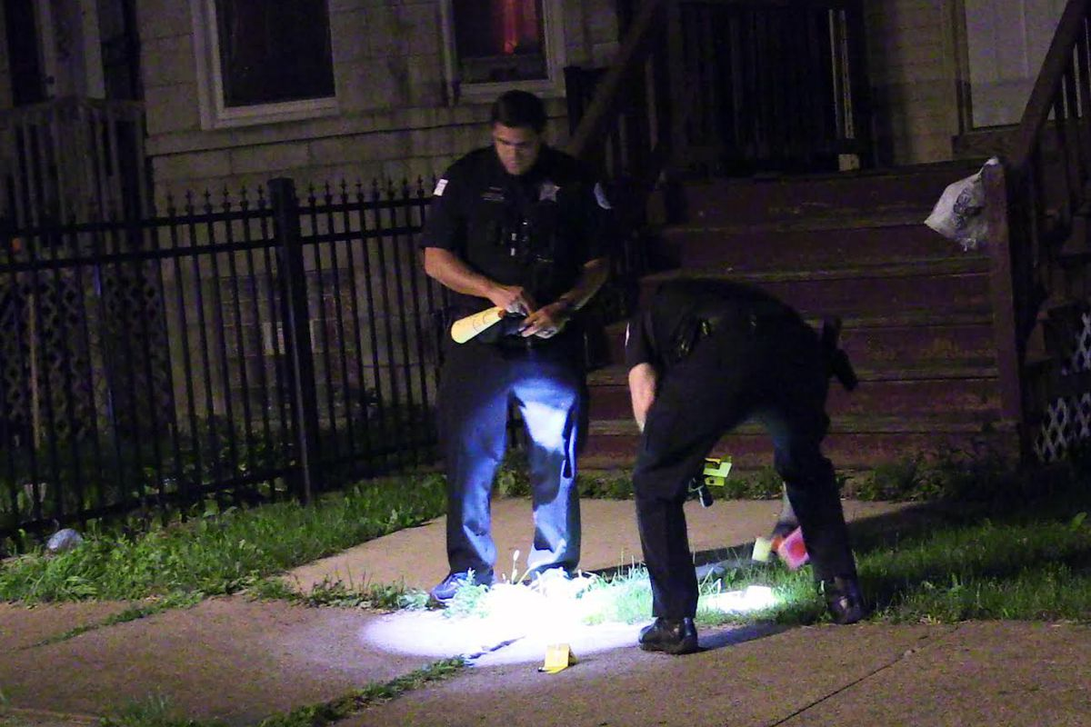 Chicago police investigate the scene where two people were shot in Austin on the West Side.