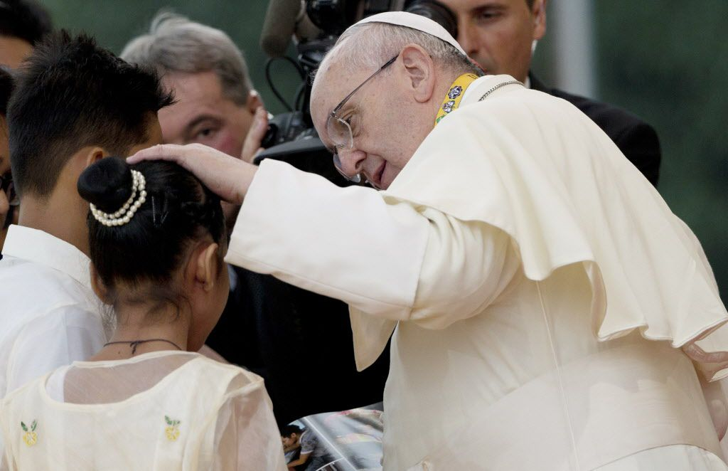 Pope Francis caresses 12-year-old Glyzelle Palomar, a rescued street child during his meeting with youths in Santo Tomas University in Manila, Philippines on Sunday. The pope ditched his prepared remarks and spoke off the cuff in his native Spanish to res