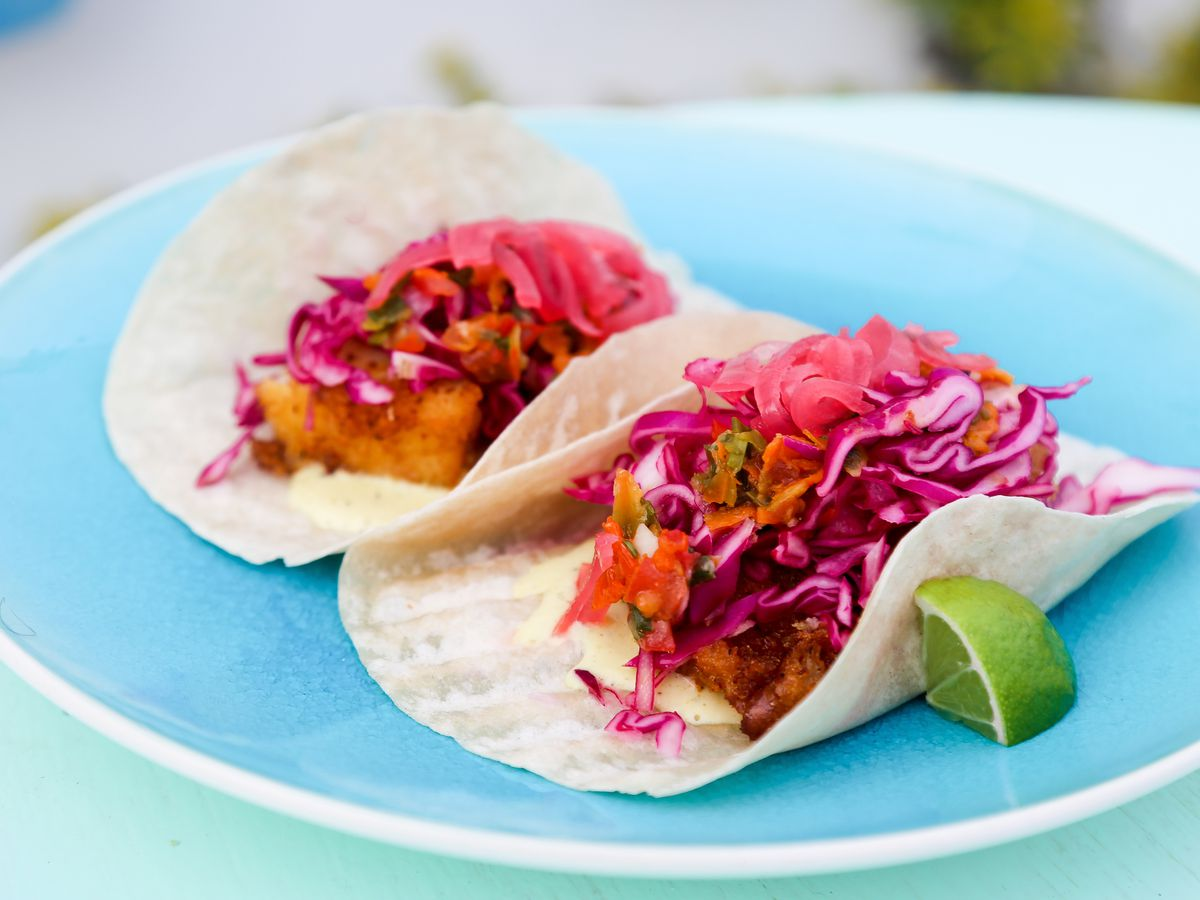 Two tacos, with fried fish barely visible beneath a pile of shredded red cabbage, sit on a bright blue ceramic plate beside a wedge of lime, on a bright formica table.