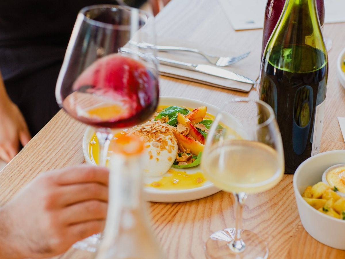 Wine swirled in a glass in the foreground with a plate of burrata on a light-wood counter in the background