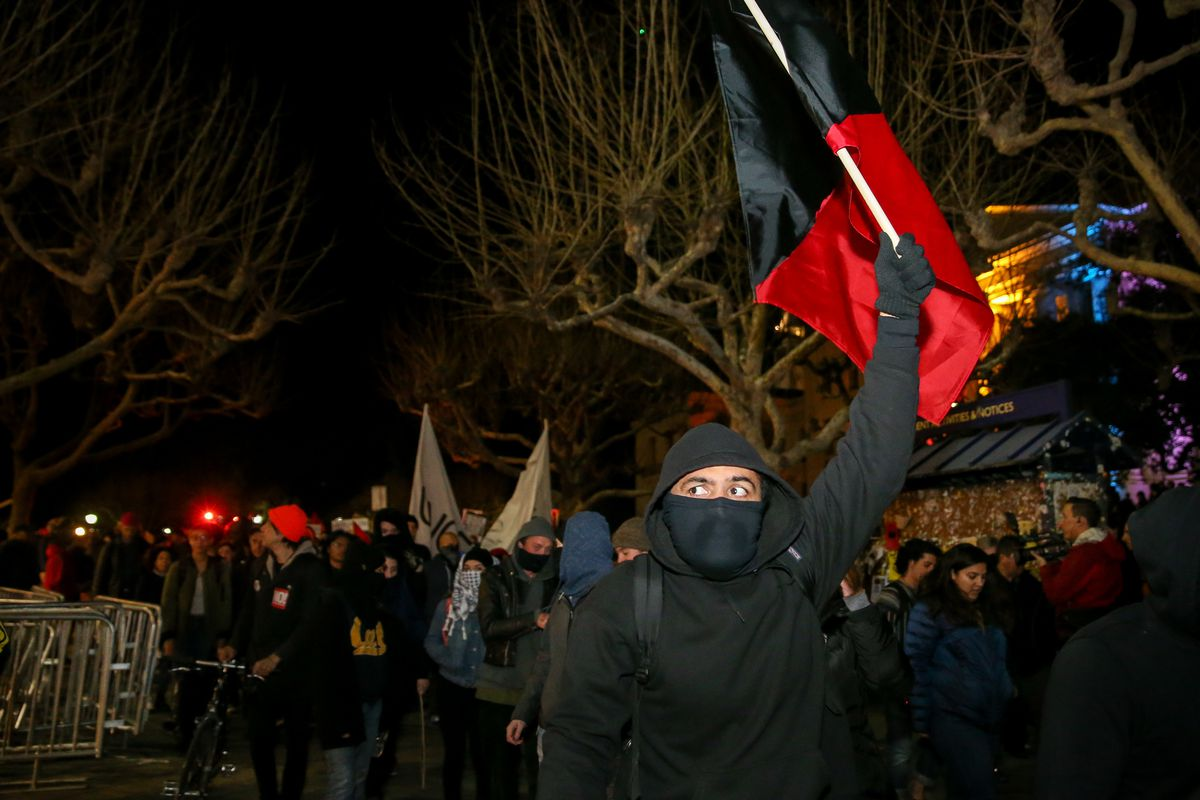 Protesters march off the UC Berkeley campus on February 1, 2017. A scheduled speech by the controversial author Milo Yiannopoulos was canceled after protesters and police skirmished.