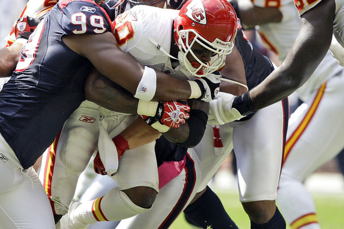 HOUSTON - OCTOBER 17:  Running back Thomas Jones #30 of the Kansas City Chiefs is tackled by Adewale Ogunleye #99 of the Houston Texans at Reliant Stadium on October 17 2010 in Houston Texas.  (Photo by Bob Levey/Getty Images)