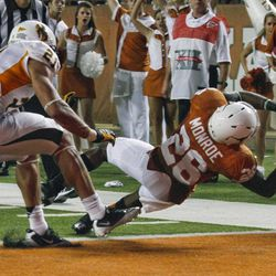 Texas' D.J. Monroe (26) scores a touchdown past Wyoming defender Mark Nzeocha during the second quarter of an  NCAA college football game, Saturday, Sept. 1, 2012, in Austin, Texas.