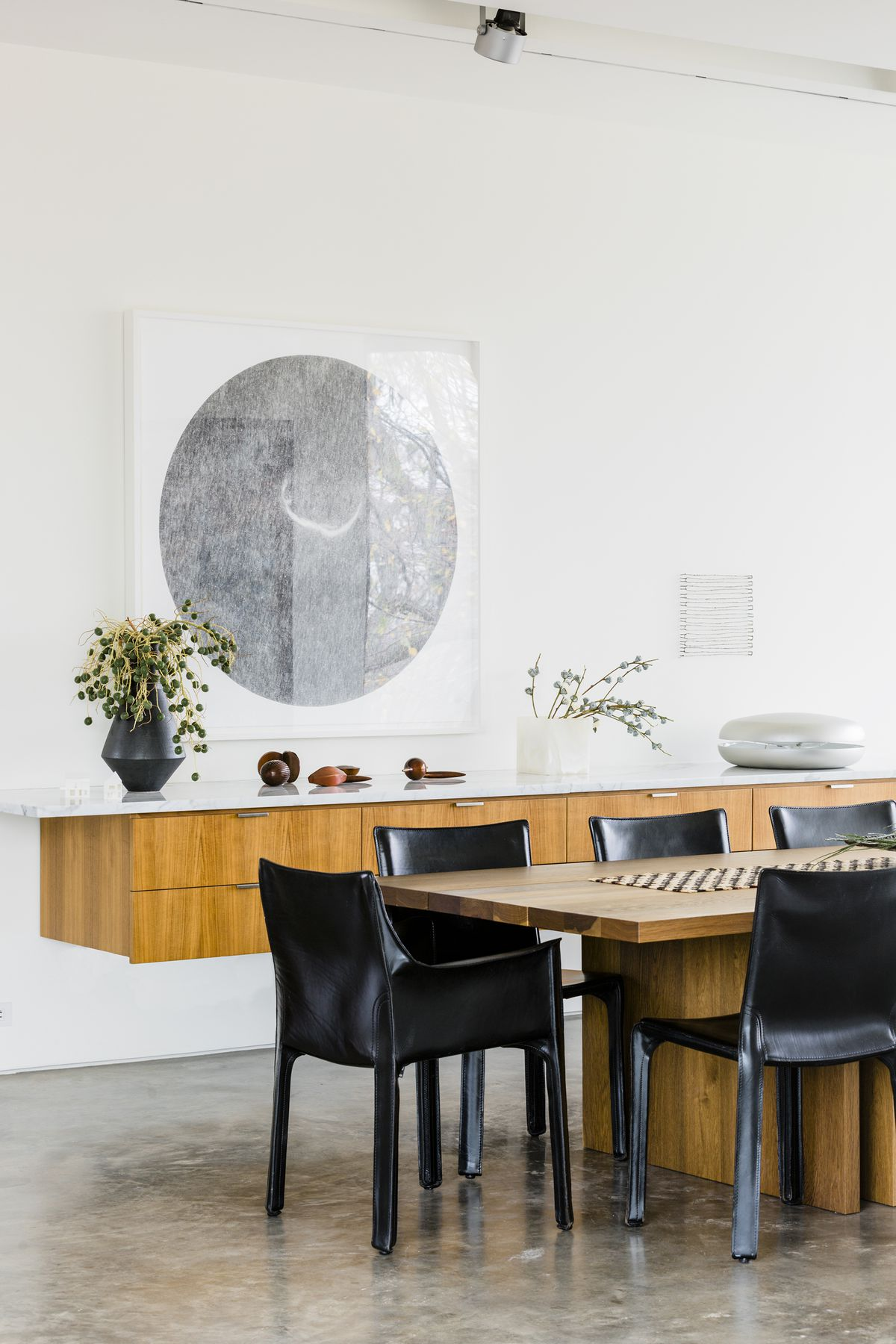 The dining room has a wood dining room table surrounded by black leather chairs. A piece of art (showing what looks like a moon) hangs above a wall-hung console.