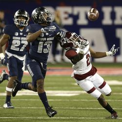Utah State cornerback Jalen Davis (13) breaks up the pass intended for Utah State quarterback Kent Myers in the second half during the Arizona Bowl NCAA college football game, Friday, Dec. 29, 2017, in Tucson, Ariz. New Mexico State defeated Utah State 26-20 in overtime. (AP Photo/Rick Scuteri)