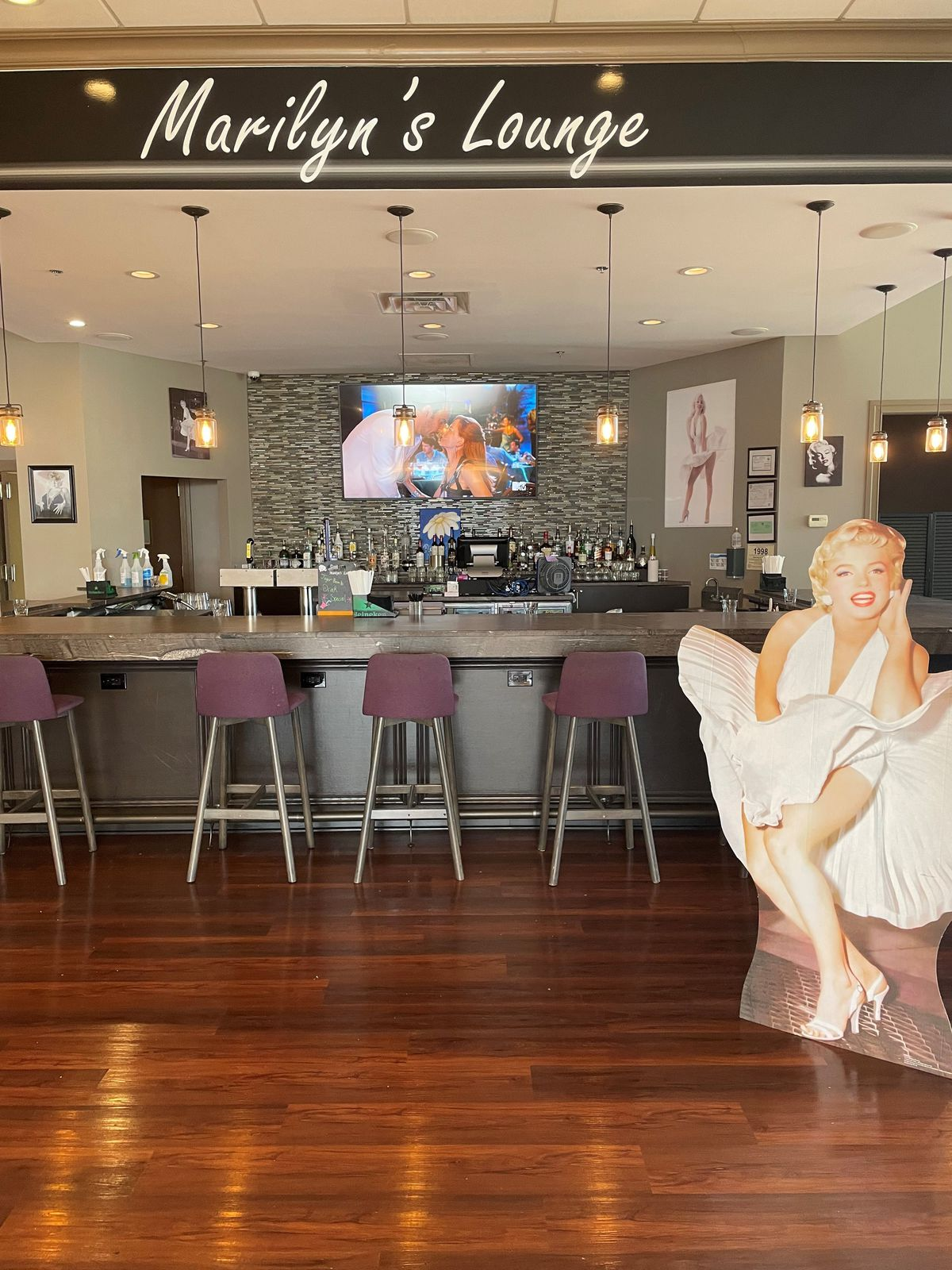 the lounge has a cardboard cutoff of Marilyn Monroe, chairs at a bar and photos of Monroe on the walls surrounding a TV
