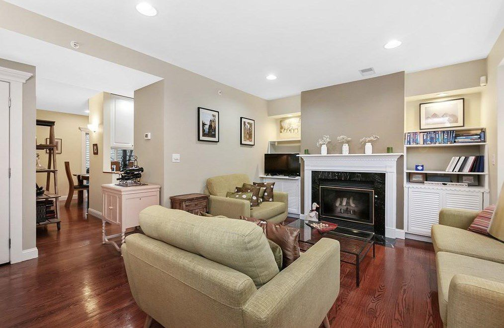 A living room with furniture arrayed toward a fireplace, and the living room opens into another room.
