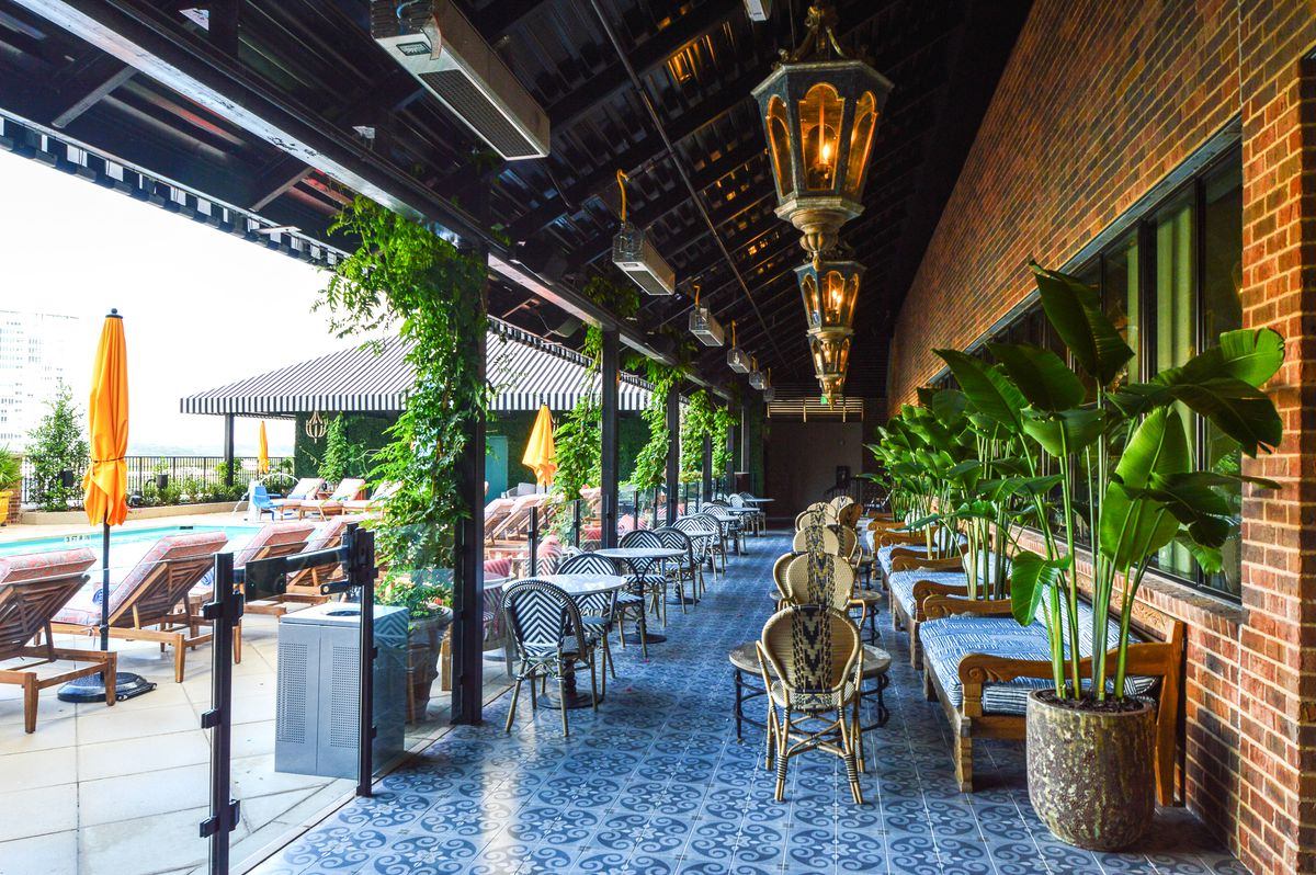 Blue tile, wicker chairs, tables, and green plants at the pool deck at Hotel Zaza