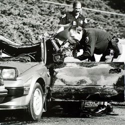 Police officers search Mark Hofmann's car after a bomb exploded at 200 North and Main Street in Salt Lake City, injuring Hofmann on Oct. 16, 1985.