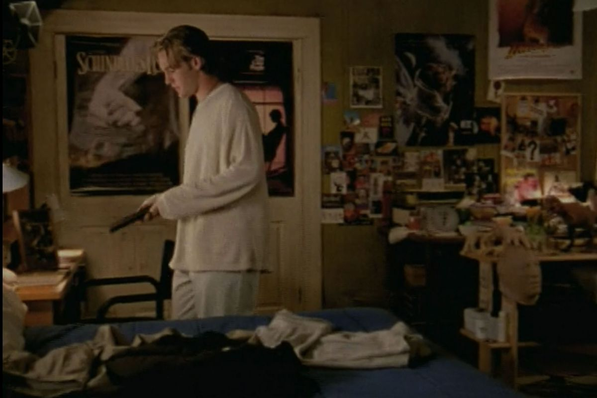 A bedroom. The walls have multiple movie posters and magazine clippings hanging. There is a desk that holds many items and objects. A teenage boy stands in the center of the room. He has a white shirt and is holding a television remote.
