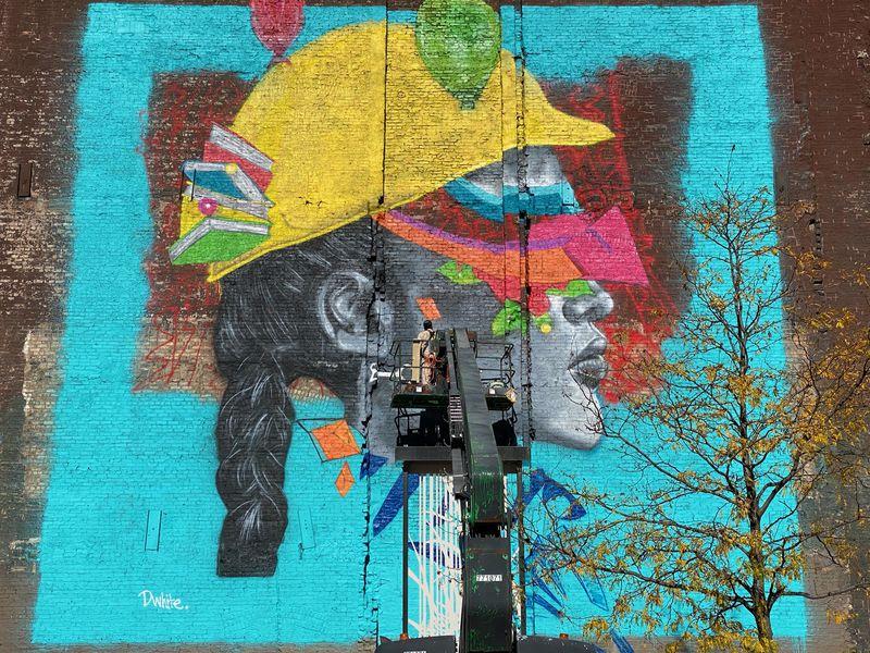 Dwight White II works on a mural on Ida B. Wells Drive this fall.