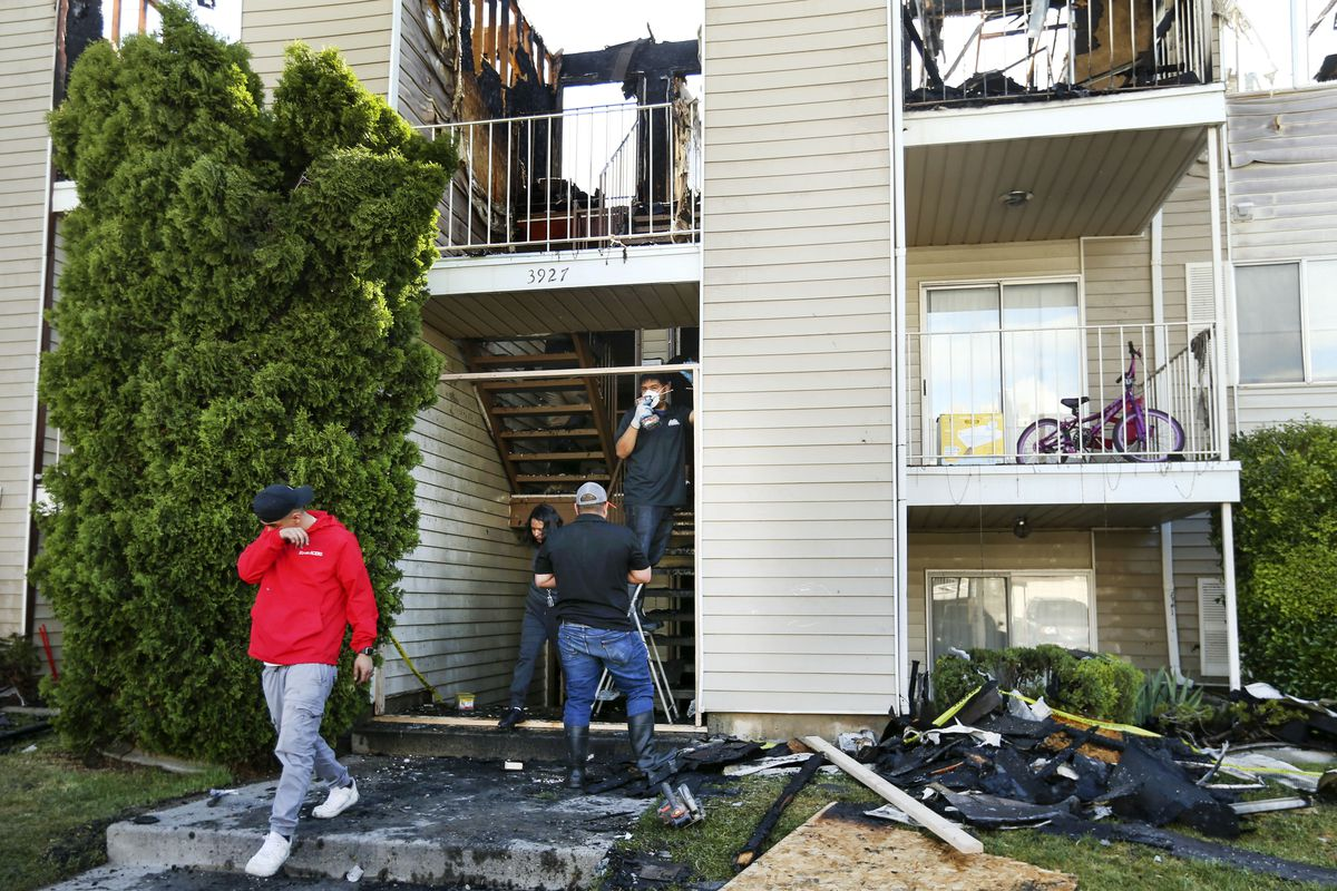 Workers clean up after an early morning fire at the Driftwood Park Apartments, 3945 S. 700 West, in Murray on Wednesday, May 20, 2020.